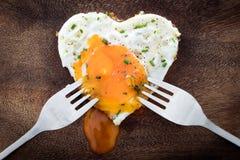 Smażący jajko z kierowym kształtem i dwa obiadowymi rozwidleniami, pojęcie miłość Obrazy Royalty Free