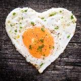 Smażący jajko z kierowym kształtem na drewnianym stole, pojęcie miłość Zdjęcia Stock