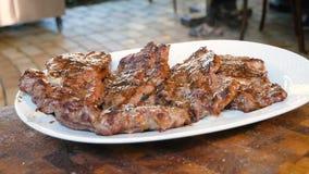 Smażący mięso kłama na białym talerzu i emituje kontrparę Gotowi mięśni stki kropią z solą przed słuzyć Restauracja zdjęcie wideo