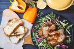 Smażący mięso, stek z sałatką, ziele, pieprz, cytryna i croutons na ciemnym drewnianym tle, Tło dla pocztówki Fotografia Stock