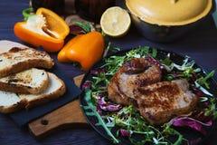 Smażący mięso, stek z sałatką, ziele, pieprz, cytryna i croutons na ciemnym drewnianym tle, Tło dla pocztówki Zdjęcia Royalty Free