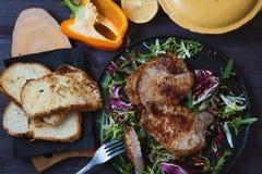 Smażący mięso, stek z sałatką, ziele, pieprz, cytryna i croutons na ciemnym drewnianym tle, Tło dla pocztówki Obrazy Royalty Free
