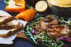 Smażący mięso, stek z sałatką, ziele, pieprz, cytryna i croutons na ciemnym drewnianym tle, Tło dla pocztówki Obraz Royalty Free
