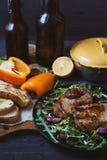 Smażący mięso, stek z sałatką, ziele, pieprz, cytryna i croutons na ciemnym drewnianym tle, Tło dla pocztówki Zdjęcie Royalty Free
