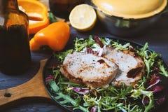Smażący mięso, stek z sałatką, ziele, pieprz, cytryna na ciemnym drewnianym tle Tło dla pocztówki Obraz Royalty Free