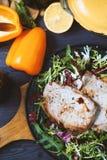 Smażący mięso, stek z sałatką, ziele, pieprz, cytryna na ciemnym drewnianym tle Tło dla pocztówki Zdjęcie Royalty Free