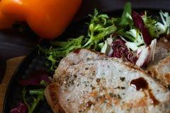 Smażący mięso, stek z sałatką, ziele, pieprz na ciemnym drewnianym tle Tło dla pocztówki Zdjęcia Stock