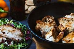 Smażący mięso w smaży niecce z sałatką, ziele, pieprz na ciemnym drewnianym tle Tło dla pocztówki Zdjęcie Royalty Free