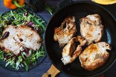 Smażący mięso w smaży niecce z sałatką, ziele, pieprz na ciemnym drewnianym tle Tło dla pocztówki Obrazy Royalty Free