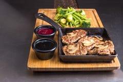 Smażący mięso z pieczarkami, sauses i warzywami na drewnianym talerzu, Zdjęcie Stock