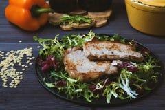 Smażący mięso z sałatką, ziele, pieprz na ciemnym drewnianym tle Tło dla pocztówki Obraz Stock