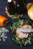 Smażący mięso z sałatką, ziele, pieprz na ciemnym drewnianym tle Tło dla pocztówki Obrazy Royalty Free
