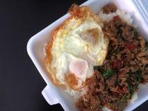 Smażący ryż z basilem z smażącym jajkiem w piany pudełku obraz stock
