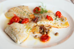 Smażący rybi polędwicowy z kaparami i pomidorami Zdjęcie Royalty Free