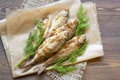 Smażący rzeka koper na papierze na drewnianym tle i ryba Obraz Royalty Free