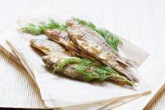 Smażący rzeka koper na papierze na drewnianym tle i ryba Zdjęcia Royalty Free