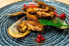 Smażący skrzydła z mussels w czarnym talerzu obraz royalty free
