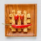Smażący tempeh dekorujący z chłodnym i pomidorowym uśmiechem na drewnianej tacy Odgórny widok Zakończenie Kwadratowy wizerunek fotografia stock