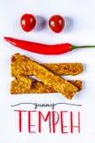 Smażący tempeh dekorujący z chłodnym i pomidorowym uśmiechem YUMMY TEMPEH podpis Odgórny widok Pionowo wizerunek obraz royalty free