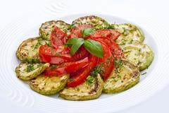 Smażący zucchini z pomidorami na białym talerzu fotografia royalty free