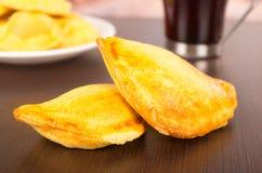 Smażę wypełniał empanadas na stole za wyśmienicie kawą, Fotografia Royalty Free