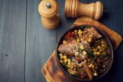 Smażeni wieprzowina kotleciki z karmelizującą kukurudzą w ciskającej żelaznej niecce i warzywami zdjęcie stock