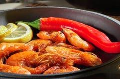Smażyć garnele z cytryną i czerwonym pieprzem w żeliwnej smaży niecce Przygotowywający restauracyjny naczynie w domu Drewniany tł Fotografia Royalty Free