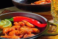 Smażyć garnele z cytryną i czerwonym pieprzem w żeliwnej smaży niecce Przygotowywający restauracyjny naczynie w domu Drewniany tł Obrazy Royalty Free