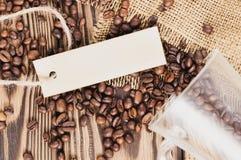 Smażyć kawowe fasole nalewali z szkła obok prostokąta pustego papieru z arkaną na hessian workowym płótnie zdjęcia royalty free