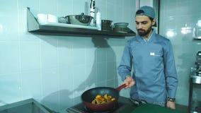 Smażyć nieckę z warzywami w szef kuchni ręce Męskiego szefa kuchni kulinarni warzywa przy restauracją zdjęcie wideo