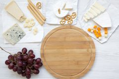 Smaczny ser z winogronami, chlebowymi kijami, orzechami włoskimi i preclami na drewnianym tle, odgórny widok Jedzenie dla romanty obrazy royalty free