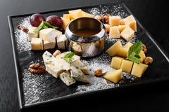 Smaczny serowy naczynie na czarnym kamienia talerzu Jedzenie dla wina i garmażerii na ciemnym wzoru stole romantycznej, serowej, zdjęcia royalty free