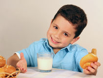 Smailing boy. A boy sitting at the teble and eating bun Royalty Free Stock Images