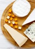 Smaka ost på runt bambubräde på en vit trätabell Mat för vin, bästa sikt Lägenhet som är lekmanna-, från över, över huvudet royaltyfri bild