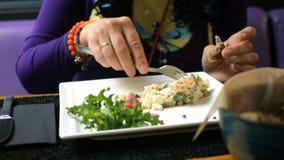 Smakelijk diner Mens die traditionele salade voor slavic volkeren Olivier of salade met groenten en vlees in koffie eet of stock video
