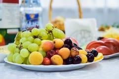 Smakelijk fruit op een plaat met kersen, druiven, abrikozen royalty-vrije stock foto's