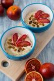 Smakelijk havermeel met Siciliaanse oranje plakken en rozijnen op blauwe kommen Royalty-vrije Stock Foto