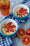 Smakelijk havermeel met Siciliaanse oranje plakken en rozijnen op blauwe kommen Stock Foto's