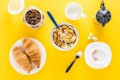 Smakelijk ontbijt met muesli, croissants en koffie op geel Royalty-vrije Stock Fotografie