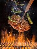 Smakelijk rundvleeslapje vlees die boven gietijzerrooster vliegen met brandvlammen stock fotografie