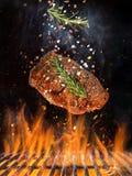 Smakelijk rundvleeslapje vlees die boven gietijzerrooster vliegen met brandvlammen stock foto