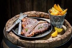 Smakelijk spaanders en riblapje vlees op oud vat Royalty-vrije Stock Afbeelding