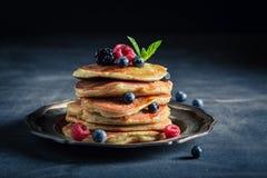 Smakelijke Amerikaanse pannekoeken met ahornstroop en bessen royalty-vrije stock fotografie