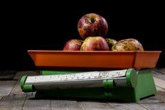 Smakelijke appelen en oude keukenschalen op een houten lijst Keuken s Stock Afbeelding