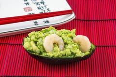 Smakelijke avocadosalade met twee garnalen en rode eetstokjes royalty-vrije stock foto's