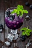 Smakelijke braambessencocktail in wijnglas met munt en ijs op donkere houten lijst De limonade van de de zomerbes Stock Fotografie