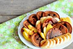 Smakelijke cacaopannekoeken met fruit Gebakken cacaopannekoeken met stroop, gesneden verse bananen en appelen op een witte plaat Royalty-vrije Stock Fotografie