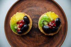 Smakelijke cakes met verse vruchten en bessen op een plaat royalty-vrije stock afbeeldingen
