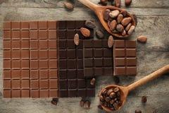 Smakelijke chocolade, cacao en koffiebonen op houten lijst, hoogste mening royalty-vrije stock afbeelding