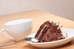 Smakelijke chocoladecake op een plaat met een kop Stock Foto